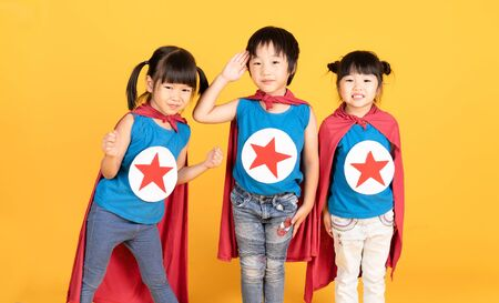 Group of Asian Kids Friendship playing superhero over colorful yellow isolated background.Superheroes and Fun Concept.Happy Time.