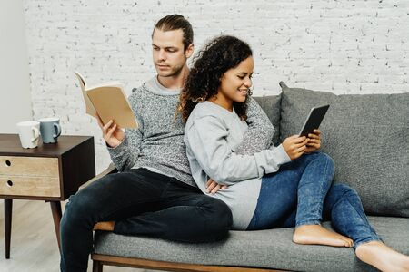 Young mixed race couple sitting on a sofa in the living room while each reads from either a book or a tablet.Couple Lifestyle Living Concept.