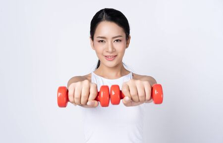 Sporting Asian woman holding dumbell in studio looking at camera in studio isolated over white background. Fitness and healthy lifestyle concept.