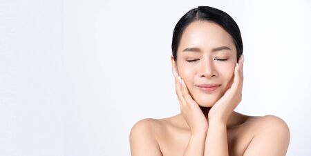 Panoramic banner image of beautiful young Asian woman with closed eyes, clean fresh skin. Cosmetology, beauty and spa concept. Isolated on white background. wide crop