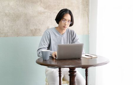 Pensive young man with eyeglasses working on laptop from home office. Business People and technology, Working Home office Concept. Stok Fotoğraf