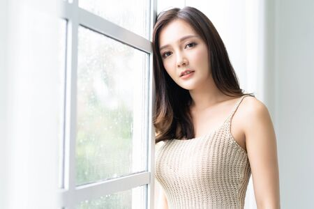 Beautiful young Asian woman leaning at the glass window with rain drops and looking at camera at her home. Morning. Mood.  Lifestyle and Relax, Emotion Concept.