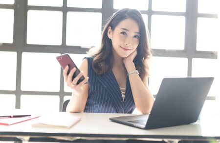 Portrait of smiling pretty young Asian business woman working on laptop at office while holding mobile phone and looking at camera in the modern office. Business, technology, communication and people concept
