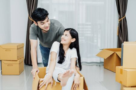 Funny young Asian couple sitting in cardboard boxes enjoy and celebrating moving to new home. People, moving and real estate concept.