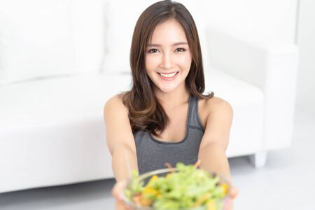 Portrait of young Asian woman in sportswear holding a glass bowl of salad in front of her while relaxing and looking at camera in living room.Fitness, Eating healthy food and people lifestyle concept.