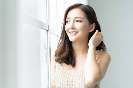 Beautiful young Asian woman leaning at the glass window and looking through window at her home. Morning. Good Mood.  Lifestyle and Relax, Emotion Concept. Banco de Imagens