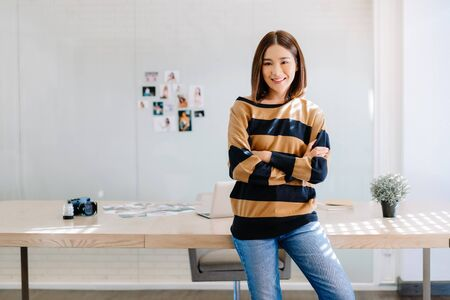 Portrait of smiling Asian woman photographer standing with arms crossed and looking at camera at her studio.Freelance Startup Small business owner, Online marketing. SME