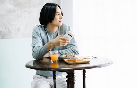 Portrait of young Asian man wearing sweater grey eating tasty breakfast and holding smartphone,looking out at the window. Concept lifestyle and technology. Autumn, winter season Banco de Imagens