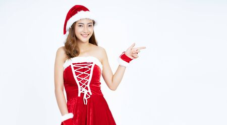 Panoramic banner image of young beautiful Asian girl dressed in Santa Claus costume points with fore finger away, indicates copy space on isolated on white background. Banner for website header design