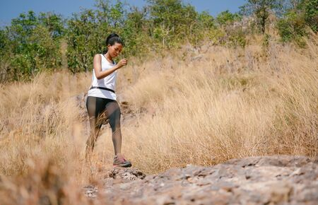 Trail runner African American woman running on outdoors in beautiful mountain nature landscape. Active health and motivation lifestyle and Adventure Concept