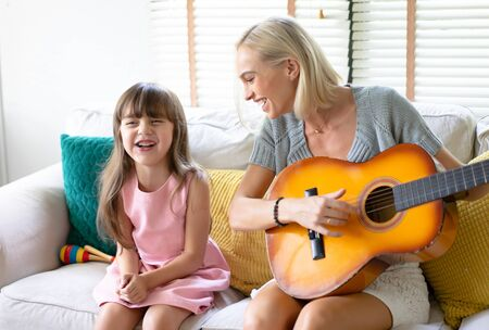Music is so much fun. Mother and daughter playing guitar together  and smiling while sitting on the sofa in living room.People and family and lifestyle mothers day concept