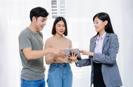 Young Asian couple with real-estate agent visiting house for sale. Deal sale or buying realty concept