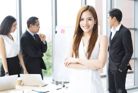 Beautiful young Asian business woman in office folded arms and confident expression as other workers hold a meeting in background.Woman leader concept. Banco de Imagens