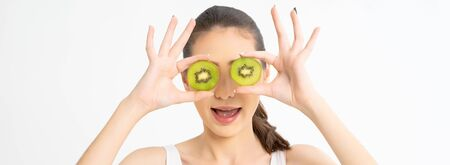Panoramic banner image of beautiful young girl holding two slices of an kiwi at her face over white wall background.Great food for a healthy lifestyle. wide crop.
