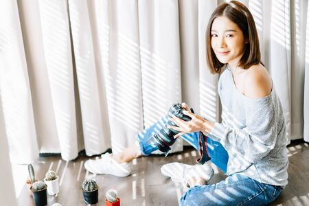 Portrait of young beautiful Asian girl photographer taking picture object shots of cactus on the floor in room studio and looking at camera. Happy Blogger and freelance working online marketing. Startup Small Business owner. SME. Banco de Imagens