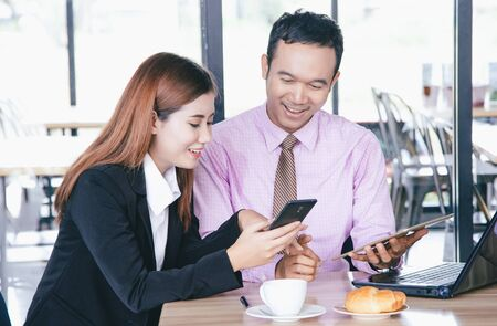 Side view of two young Asian business people using a laptop and looking at a digital tablet and smile while working at cafe. Business, people and Modern technology or internet gadget devices concept. Banco de Imagens