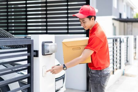 Portrait of young delivery Asian man bringing some packages to the front door and ringing the doorbell outdoors.Delivery and Package concept.