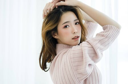 Portrait of inspired beautiful Asian lady in warm knitted sweater pink clothes at home.Concept woman lifestyle and winter. Autumn, winter season.