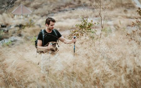 Portrait of young man hiker with backpack and sticks walking on a mountain, trekking poles enjoying a freedom. Camping activity. Concept of adventure, trekking and seasonal vacation. Banco de Imagens