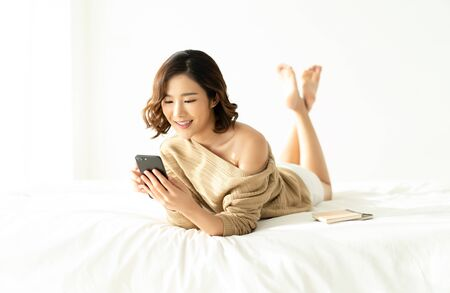 Portrait of smiling young Asian woman wearing knitted sweater beige cold using a mobile phone lying down on white bed. Beautiful girl typing on smartphone and surfing the net.Concept woman lifestyle and winter.