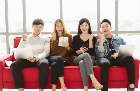 Yes! Group of Students or teenagers using digital devices and howing triumph gesture and looking at camera in university atrium social networking using several tech devices.Technology , education and teenage concept.