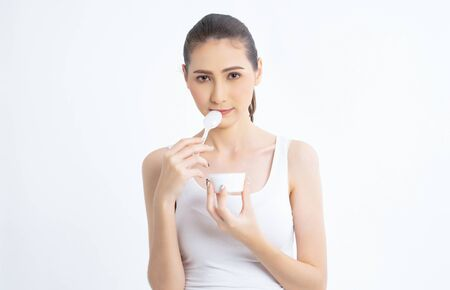 Healthy Diet And Nutrition. Beautiful young woman eating organic yogurt on white background.Dairy Food. High Resolution