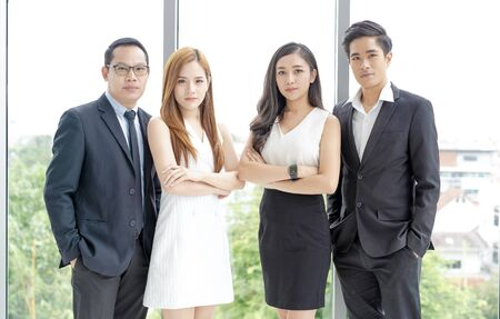Successful Asian business team is looking at camera and while standing with crossed arms in office.Teamwork business concept.
