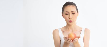 Portrait of a cheerful young woman with red apple isolated over white banner background with copy space for Healthy food. Skin care and beauty. Vitamins and minerals.Banner panorama.