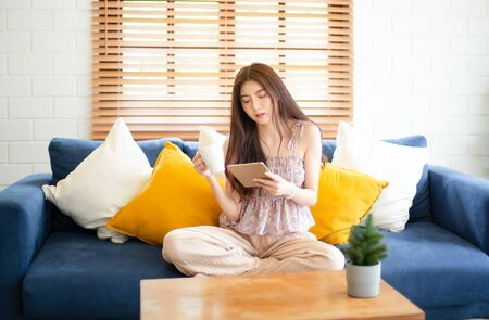 Portrait of young beautiful Asian woman at home sitting on the couch using tablet and drinking cup of hot coffee or tea in her living room. Lifestyle and relaxation, Communication and technology concept.