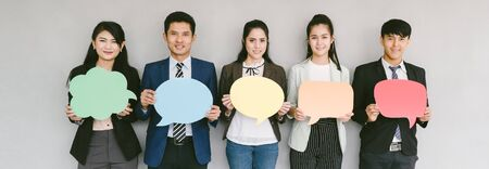 Group of business people while holding up speech bubble icons on gray banner background. wide crop