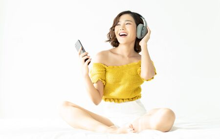 Happy beautiful young Asian woman sitting on bed and listening to music with headphones connected to smartphone. Concepts of home and lifestyle, comfort.