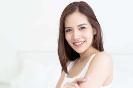 Beautiful Asian woman applying body lotion on her attractive arm during her morning routine and looking at camera in bedroom. Skin Care, Beauty, Wellness and health Concept