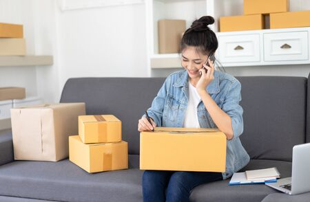 Portrait of young Asian casual woman working small business online packing her talking with customer on mobile phone and note orders at home office. Startup Small business owner, Online Selling, SME Business, freelance working concept.