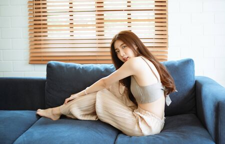 Young beautiful Asian woman sitting on the couch and looking at camera in her living room at home.Lifestyle and relaxation concept.
