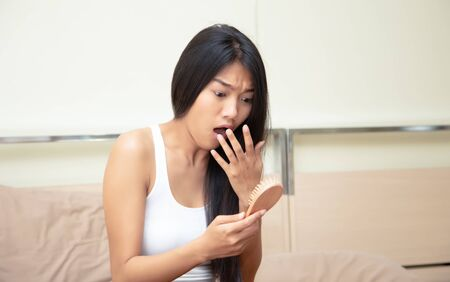 Worried young Asian woman Suffering From Hairloss Looking At Comb, Hair loss problem in her bedroom. Banco de Imagens