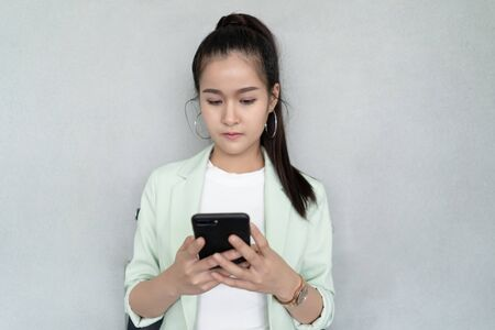 Portrait of a Asian businesswoman sitting on the chair and writing message on smartphone over cement background Banco de Imagens