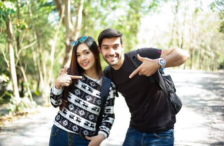 Young couple of travelers with backpacks looking at camera in the sunny forest. Adventure, travel, tourism, hike and people concept.