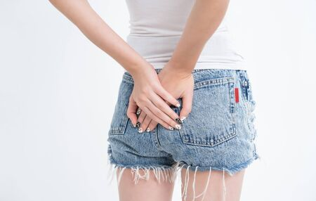 Close up of Young woman with long nail in jeans shorts holding hands on her ass isolated over white background.