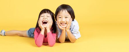 Two Happy Asain kids lying on the floor and touches cheeks with both hands, has broad smile, shows perfect teeth over yellow lights banner background. Banner panorama.