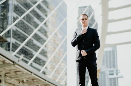 Portrait of happy smiling young businessman in a stylish suit standing and adjusting his neck tie on front building office. Banco de Imagens