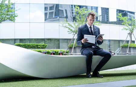 Portrait of businessman sitting on a bench and holding tablet and file at business center. Concept of work life balance.