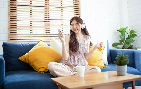 Teenager Asian girl sitting on the sofa listening to music with stylish white headphones and dancing.Lady having fun while listens her favorite songs. People lifestyle and relax time, Lazy day off concept.