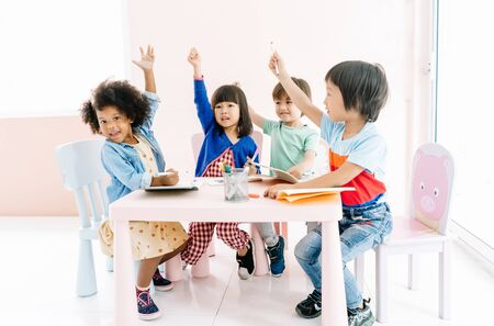 Group of adorable kids diverse cultures colored pencils painting on art drawing paper and raise arm up to answer teacher question in the kindergarten. Preschool international,education concept. Banco de Imagens