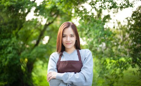Beautiful Asian woman confectioner with long hair standing with arms crossed outside the flower shop owner. Startup of small business owner and service mind concept.
