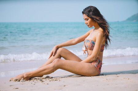 Beautiful Asian woman body in sexy bikini over beach background. Long dark hair, perfect figure, tropical lifestyle, Summer holidays concept. Banco de Imagens