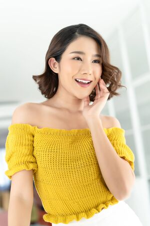 Beautiful young Asian woman caring of her beautiful skin on the face  with natural makeup and smiles happily as enjoys great morning and starting new day in her bedroom.Beauty and Skincare Concept. Banco de Imagens
