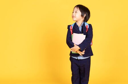 Happy little Asian child boy standing with holding books and looking away on isolated over yellow background. First time to school. Back to school. Education concept. Copy Space.