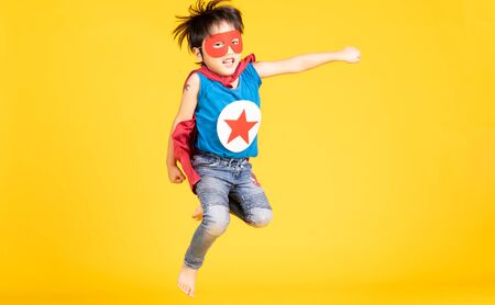 Happy little Asian child boy playing superhero jumping on isolated over yellow wall background. Superhero , Success and winner concept. Happy Time. Copy Space. Banco de Imagens