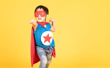 Cute little Asian child boy playing superhero on the yellow wall background. Superhero , Success and winner concept. Happy Time. Copy Space.