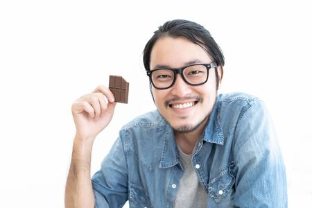 Happy young bearded hipster Asian man in eyeglasses eating a chocolate bar isolated over white background.